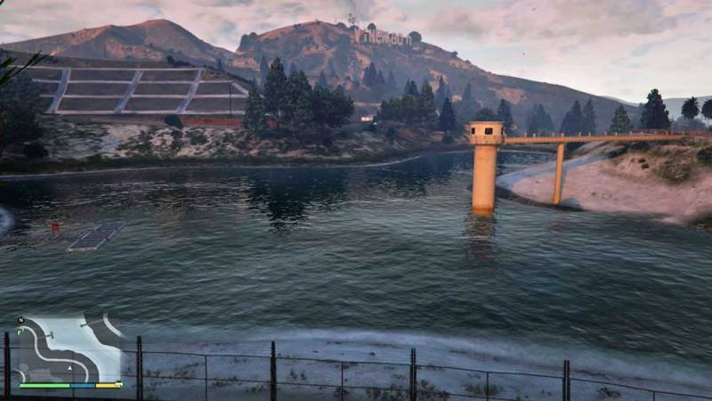 Photo: A reservoir in the game, with valve tower to the right and some possible recreational infrastructure to the left. In the background is the 'Vinewood' sign - GTA's take on Hollywood!